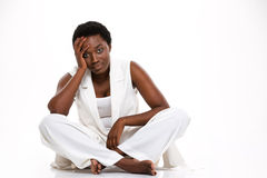 Tired african woman sitting with legs crossed and having headache Royalty Free Stock Images