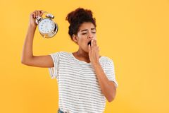 Tired african woman yawns and holding alarm clock stock image