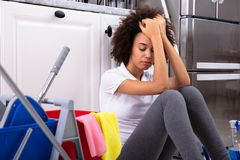 Tired African Young Woman Sitting In The Kitchen stock photos