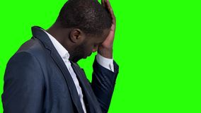 Tired afro american businessman on green screen. Exhausted dark-skinned entrepreneur on Alpha Channel background. Young man having headache stock video footage