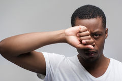 Tired afroamerican man portrait on grey background Stock Images