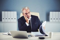 Bored businessman looking at pile of documents. Tired aged male in black business suit sitting at office desk propping face and turning pages of large pile of Royalty Free Stock Images
