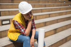 Tired American female engineer in city. Tired American female engineer with white helmet hat and engineering paper blueprint sit and take a nap or sleep at royalty free stock photography