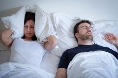 Tired and annoyed woman of her boyfriend snoring in bed. Tired and annoyed women of her boyfriend snoring in the bed Royalty Free Stock Images