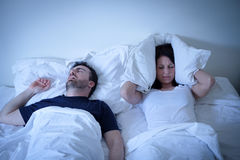 Tired and annoyed woman of her boyfriend snoring in bed. Tired and annoyed women of her boyfriend snoring in the bed Stock Images