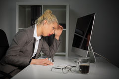 Tired and annoyed woman working on computer at the office Stock Photos