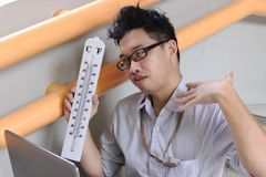 Tired Asian business man with thermometer sitting and sweating after work. Summer heat day concept stock photos