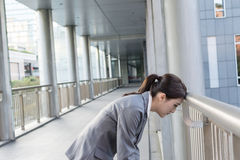 Tired Asian business woman put head on balustrade Royalty Free Stock Photo