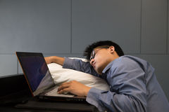 Tired Asian businessman sleeping on a laptop with pillow Royalty Free Stock Photos