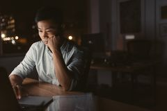 Tired Asian businessman working at his desk late at night Stock Image