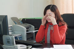 Tired Asian businesswoman. Tired young Asian businesswoman sat at desk in office rubbing eyes Royalty Free Stock Photography