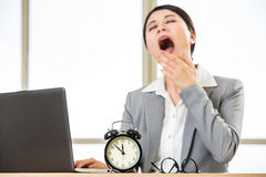 Tired Asian businesswomen yawing at desk, overtime and overworke Stock Photo