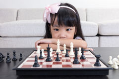 Tired Asian Chinese little girl playing chess at home Royalty Free Stock Image