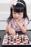 Tired Asian Chinese little girl playing chess at home Stock Images