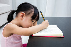 Tired Asian Chinese little girl writing on exercise book Stock Images
