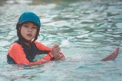 Tired Asian kid girl sitting in kid swimming pool royalty free stock photo
