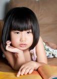Tired asian little girl feel sleepy near book Royalty Free Stock Photo