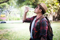 Tired asian man with backpack drinking water. royalty free stock image