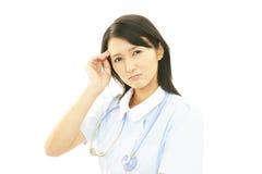 Tired Asian nurse stock image