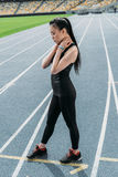 Tired asian sportswoman standing on running track stadium and looking down. Young tired asian sportswoman standing on running track stadium and looking down Stock Images
