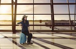 Tired asian traveler woman sitting on luggage waiting flight Stock Photos