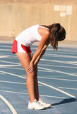 Tired athlete. Tired girl on a blue racetrack Royalty Free Stock Photo