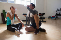 Tired athletes drinking water while sitting in gym Stock Photography