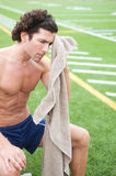Tired athletic male runner in stadium. Tired athletic male runner sitting in a stadium Stock Image