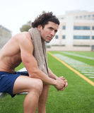 Tired athletic male runner in stadium. Tired athletic male runner sitting in a stadium Royalty Free Stock Photo
