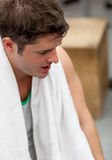 Tired athletic man standing with a towel Stock Image