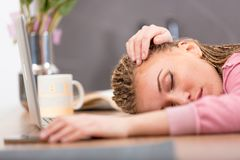 Tired attractive young woman sleeping on a table royalty free stock images