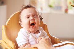 Tired Baby In High Chair At Meal Time Royalty Free Stock Photos