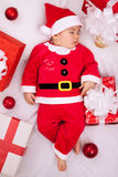 Tired baby santa resting on presents Stock Images