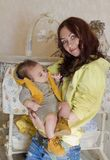 Tired babysitter with baby in her arms in bedroom. Women holding a sleeping son in her arms stock images