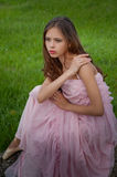 Tired ballerina in pointe which sits in the grass Royalty Free Stock Images
