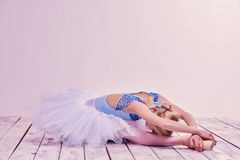 Tired ballet dancer lying on the wooden floor Stock Photos