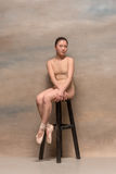 Tired ballet dancer sitting on the wooden chair on a pink background Royalty Free Stock Images