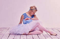 Tired ballet dancer sitting on the wooden floor Royalty Free Stock Images