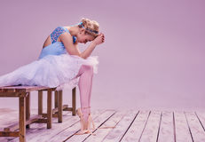 Tired ballet dancer sitting on the wooden floor Royalty Free Stock Photography