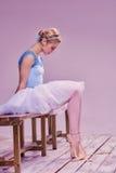 Tired ballet dancer sitting on the wooden floor Stock Images