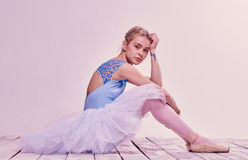 Tired ballet dancer sitting on the wooden floor Stock Images