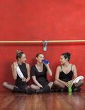 Tired Ballet Dancers Sitting On Hardwood Floor. In training studio Stock Photo