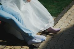 Tired barefoot wedding couple is sitting. In the park on the bench. Groom and bride in socks without shoes royalty free stock photography