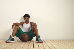 Tired basketball player sitting on the floor against the wall Royalty Free Stock Photos