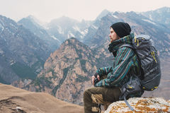 Tired bearded hipster with binoculars in his hands sits on a stone among the mountains and looks out into the distance Royalty Free Stock Images
