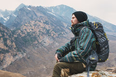 Tired bearded hipster with binoculars in his hands sits on a stone among the mountains and looks out into the distance Stock Image