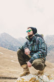 Tired bearded hipster with binoculars in his hands sits on a stone among the mountains and looks out into the distance Royalty Free Stock Photos