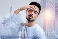 Tired bearded man touching his forehead while feeling unwell. Feeling dizzy. Young exhausted bearded man standing with his eyes closed and touching his forehead Royalty Free Stock Photo
