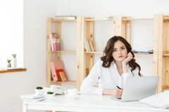 Tired beautiful Businesswoman holding hand on head while working on computer and some business documents in bright. Office royalty free stock photography