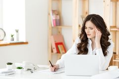 Tired beautiful Businesswoman holding hand on head while working on computer and some business documents in bright. Office stock images